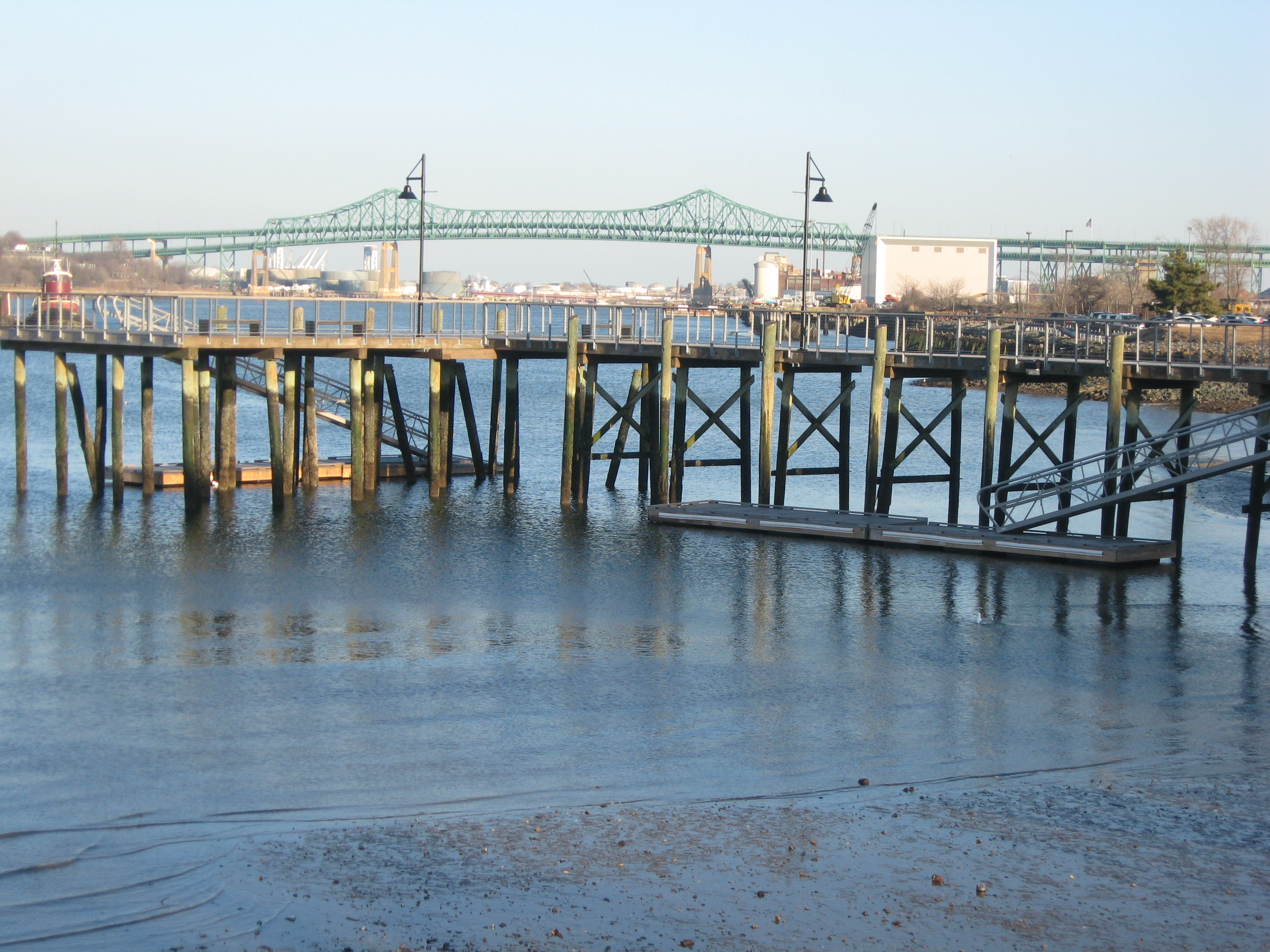 Low tide on the Mystic estuary with pier and Tobin bridge.